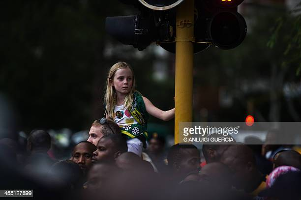 A South African girl sits on the shoulders of her father as South Africans sing an dance reacting to the news that the remains of late South African...