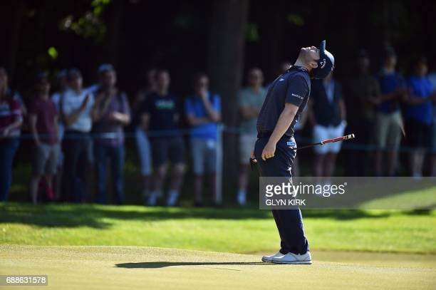 South African golfer Branden Grace reacts after putting on the first green on the second day of the golf PGA Championship at Wentworth Golf Club in...