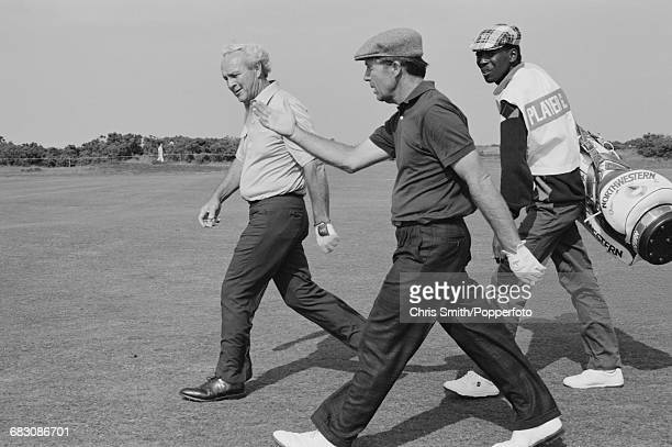 South African golfer Gary Player and American golfer Arnold Palmer on left pictured walking together with Gary Player's caddy along a fairway during...
