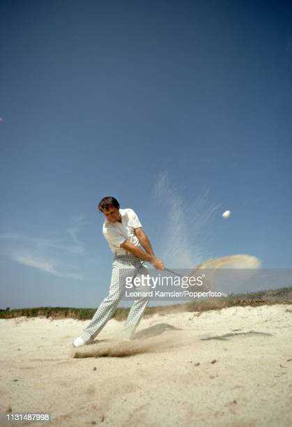 South African golfer Gary Player playing out of a bunker circa 1974