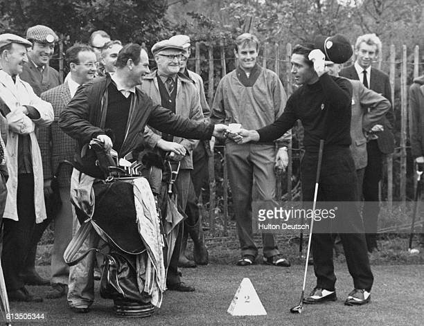 South African golfer Gary Player receives a @1 tip from his caddy Alfred Fyles after the latter was paid over @1000 by American golfer Gary Brewer...