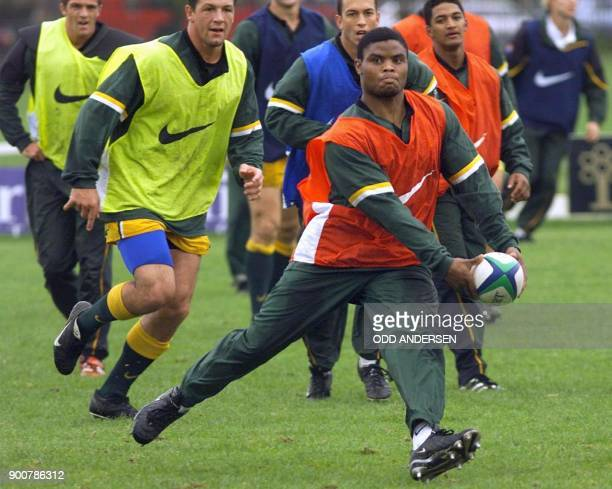 South African Kaya Malotana pursued by teammates Percy Montgomery Andre Vos Werner Swanepoel and Breyton Paulse runs with the ball during a training...