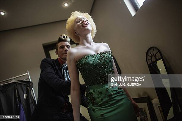 South African lawyer and parttime fashion model Thando Hopa an albino tries on an evening dress by South African fashion designer GertJohan Coetzee...