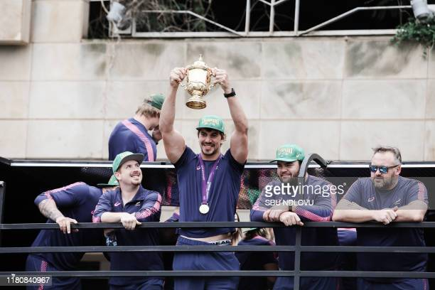 South African lock Eben Etzebeth holds up the Web Ellis trophy as the World Cup winner team parades in the Durban CBD on an open top bus in Durban on...