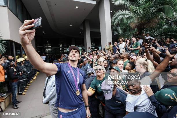 South African lock Eben Etzebeth takes a selfie with supporters as the World Cup winner team parades in the Durban CBD on an open top bus in Durban...