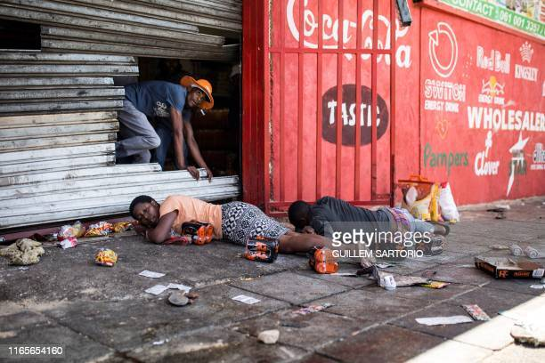 TOPSHOT South African looters lay on the ground after South African Police officers intervened during a riot in the Johannesburg suburb of...
