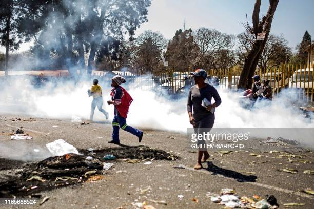 South African looters run through tear gas smoke during a riot in the Johannesburg suburb of Turffontein on September 2 2019 as angry protesters loot...