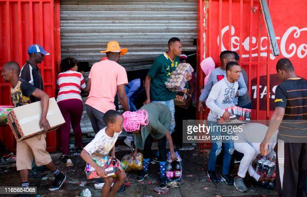 TOPSHOT South African looters take items from an alleged foreignowned shops during a riot in the Johannesburg suburb of Turffontein on September 2...