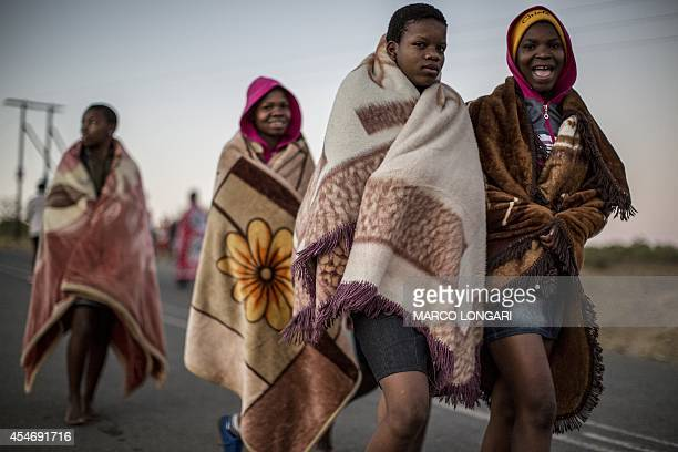 South African maidens wrap themselves in blankets as they head to a ritual bath in a local river on September 5 2014 at the eNyokeni Royal Palace in...