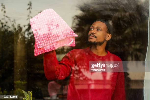 south african man cleaning a window while self-isolation - webfluential stock pictures, royalty-free photos & images