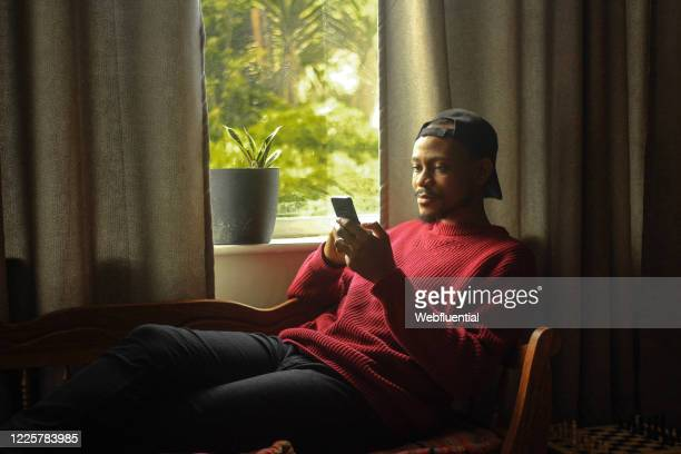 south african man sitting on a couch while texting during the covid-19 pandemic - webfluential stock pictures, royalty-free photos & images