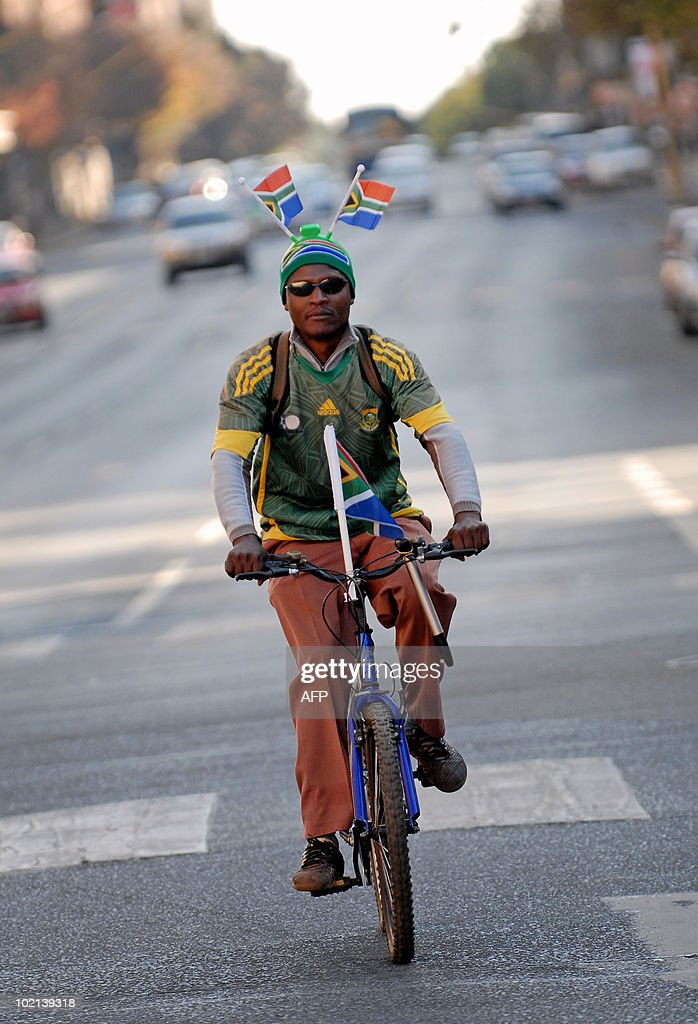 A South African man with flags flying from his headgear rides his bicycle along a street in Pretoria on June 16, 2010 just hours before the 2010 World Cup football match between South Africa and Uruguay. AFP PHOTO / Monirul Bhuiyan