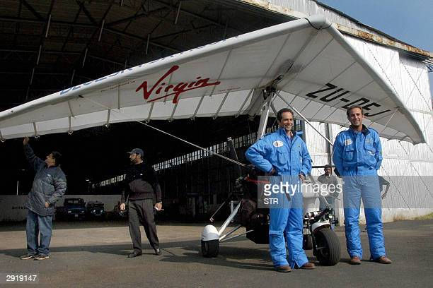 South African microlight pilots Ricky de Agrela and Alan Honeyborne stand in front of their aircraft as Indian groundstaff check the airworthiness of...