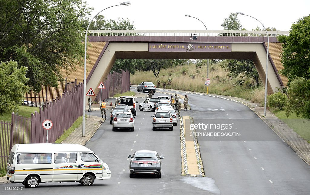 South African military police officers check cars entering the 1 Military Hospital in Pretoria where South Africa's former President Nelson Mandela is hospitalised on December 11, 2012. Nelson Mandela has a lung infection but is responding to treatment, the South African government said today, as the revered anti-apartheid icon spent his fourth day in hospital.
