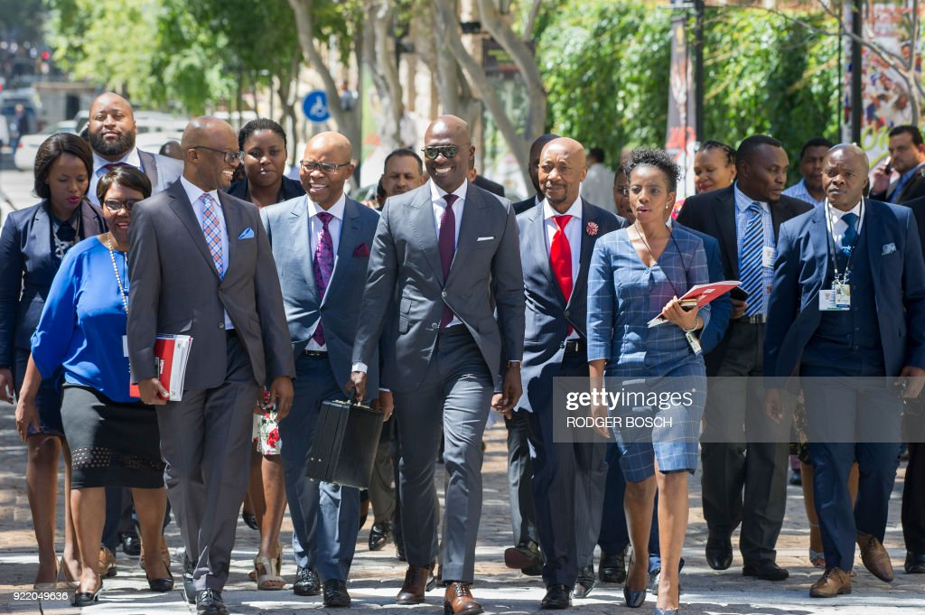 South African Minister of Finance Malusi Gigaba (C with sunglasses), walks with members of the Finance Ministry, S'fiso Buthelezi(C-R), and South African Revenue Service head, Tom Moyane (C-L), towards the National Assembly at the South African Parliament to deliver the 2018 Budget Speech, on February 21, 2018, in Cape Town. /