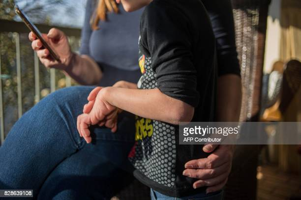 A South African mother holds her son affected by Costello syndrome and currently treated with cannabis oil at their home on July 18 2017 in...