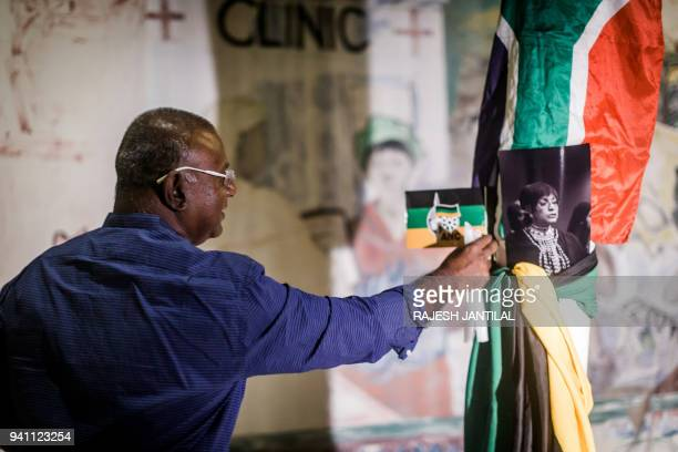 A South African mourner places an African National Congress flag on a pole near the Old Durban Prison's Human Rights wall as he pays his respect to...