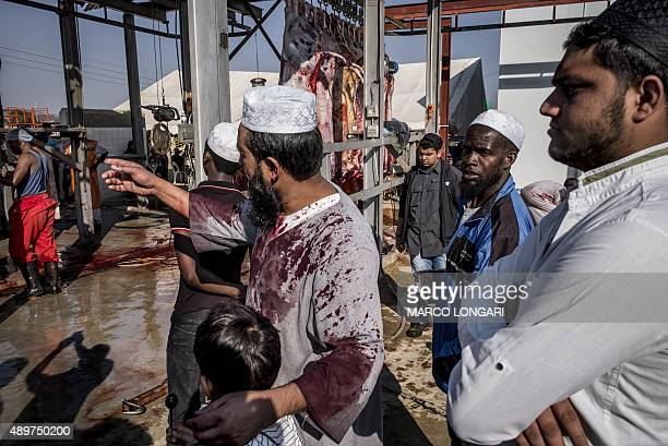 A South African Muslim stands with his child his jalabiya stained with blood from a bull as they gather during a ritual slaughter at a halal abattoir...