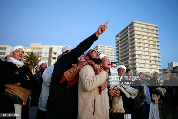 South African muslims gather on the beach front in Cape Town on June 28 as they try to spot the new moon signalling the commencement of the holy...