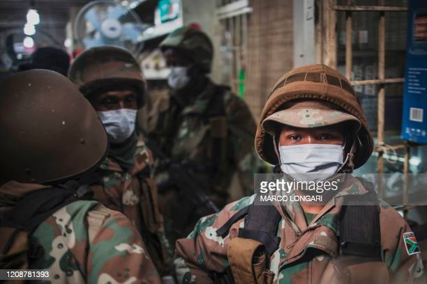 South African National Defence Force patrol check the permit of a shop in the Johannesburg CBD, on April 1, 2020 during a lockdown enforcing...