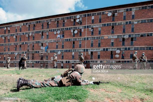 South African National Defence Force soldiers takes position outside the renowned Madala hostel in Alexandra township on March 28 during the second...