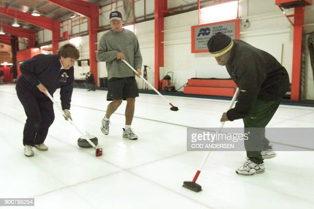 South African national rugby team player Kaya Malotana teammate Andre Vos and an unidentified curling player sweep the ice to gain momentum for their...