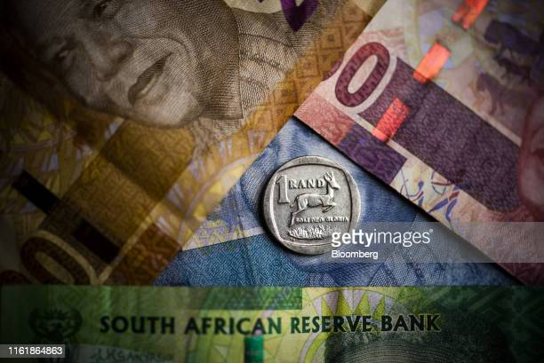 South African one rand coin sits on South African rand banknotes in this arranged photograph in Pretoria, South Africa, on Wednesday, Aug. 14, 2019....