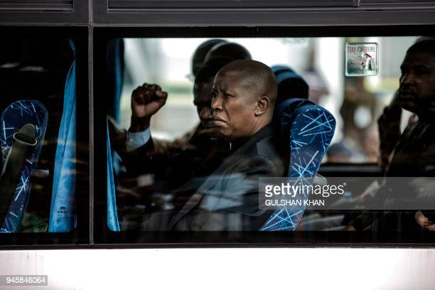 South African opposition party Economic Freedom Fighters leader Julius Malema sits in a bus with other pall bearers while mourners line the streets...