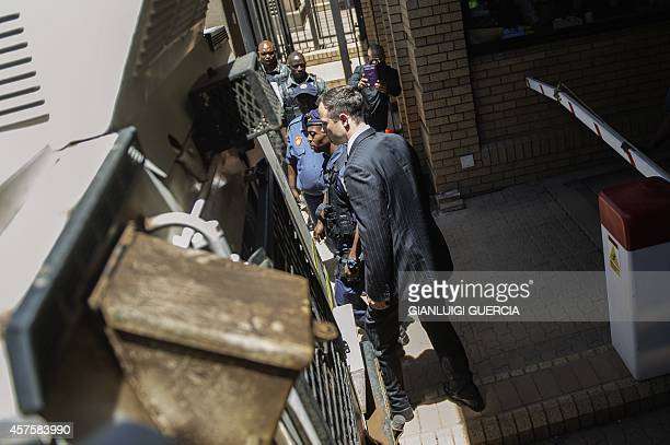 South African Paralympian athlete Oscar Pistorius is escorted by south african policemen to a police vehicle to transported to prison at the High...
