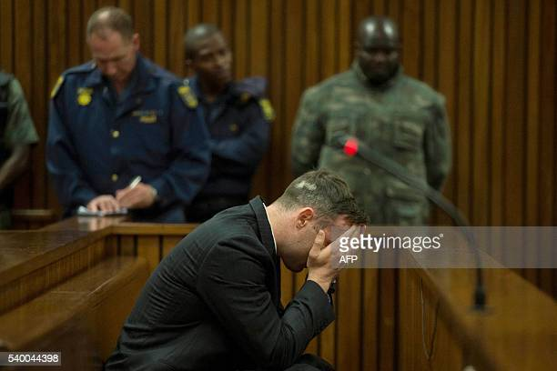 TOPSHOT South African Paralympian Oscar Pistorius covers his eyes as the father of his late girlfriend testifies at the Pretoria High Court on June...