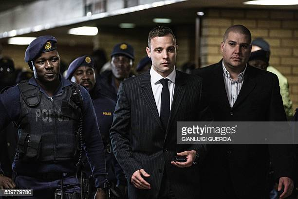 South African Paralympian Oscar Pistorius is surrounded by policemen as he arrives at Pretoria High Court to attend a sentencing hearing set to send...