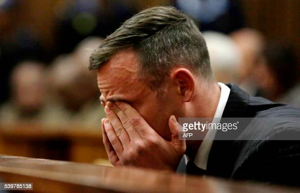 South African Paralympian Oscar Pistorius reacts as he sits in the dock during his sentencing hearing at the Pretoria High Court for murdering his...