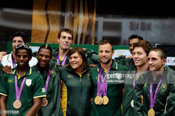 South African Paralympic athletes Natalie Du Toit and Oscar Pistorius pose with their medals during the South African Paralympic team arrival at OR...