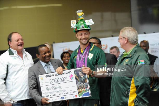South African Paralympic Gold Medal winning sprinter Oscar Pistorius receives a cheque of R700000 from Minister of Sports Fikile Mbalula as Gert...