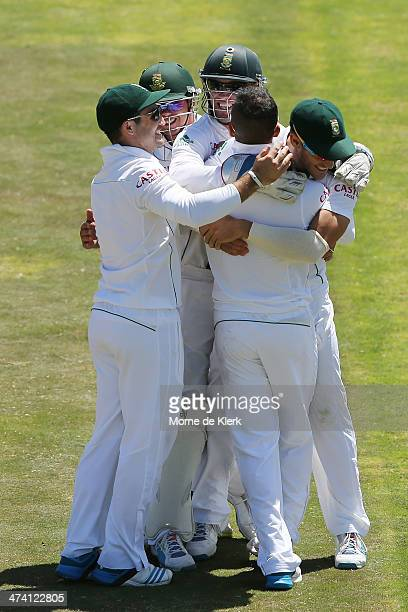 South African players congratulate JP Duminy after he bowled out Mitchell Johnson of Australia during day three of the Second Test match between...