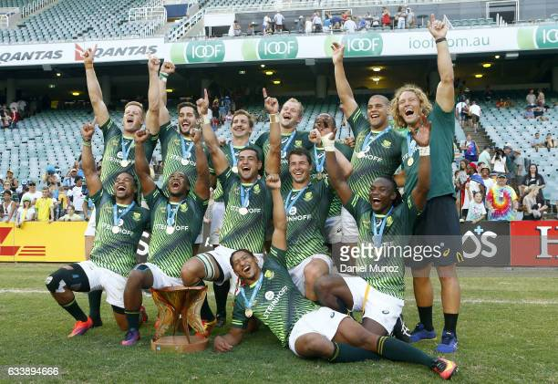 South African players pose with their trophy after winning the Men's Final match against England in the 2017 HSBC Sydney Sevens at Allianz Stadium on...