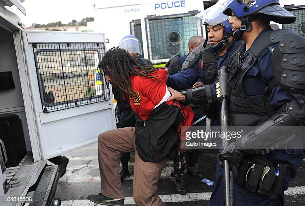 South African police arrest residents of the informal settlement Hangberg after violence broke out in Hout Bay near Cape Town South Africa on 21...