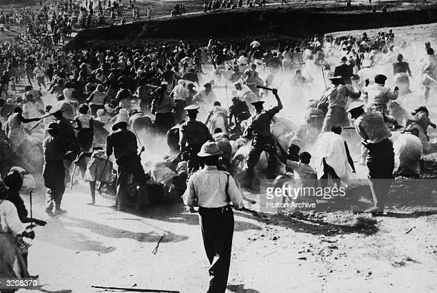 South African police beating Black women with clubs after they raided and set a beer hall on fire in protest against apartheid Durban South Africa