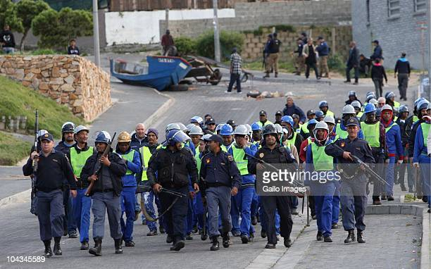 South African Police escort council workers after violence broke out in Hout Bay near Cape Town South Africa on 21 September 2010 when community...
