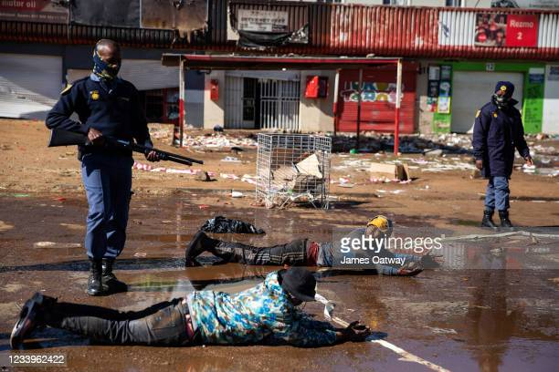 South African police force suspected looters to lie down and roll in muddy water after apprehending them on July 13, 2021 in Soweto, Johannesburg,...