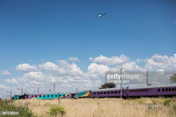 A South African Police helicopter hovers over derailed train carriages after an accident near Kroonstad in the Free State Province some 110kms...