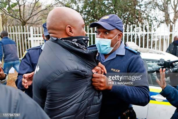South African police member grabs a protestor during their picket against the government of Zimbabwe's alleged state corruption, media freedom and...