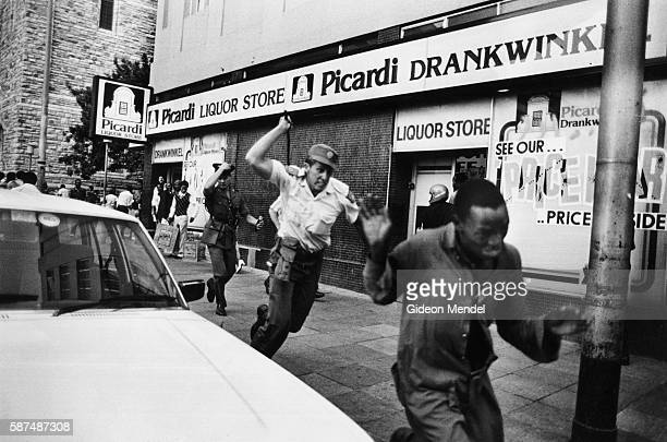 A South African police officer charges after a United Democratic Front demonstrator with a sjambok whip during a Front demonstration in Johannesburg...