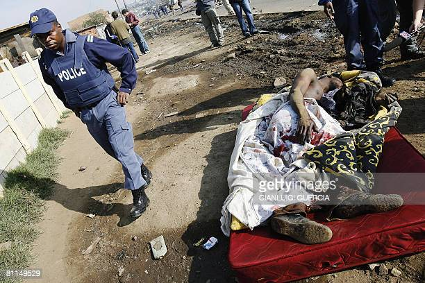 A South African police officer walks on May 19 2008 past an unidentified Malawi national as he lies in a pool of blood after beeing heavily beaten...