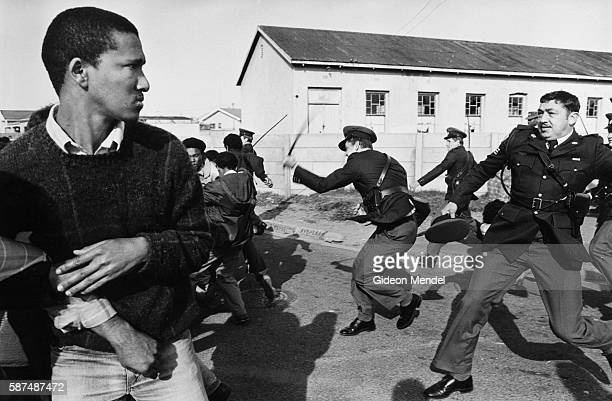 South African police officers charge a group of United Democratic Front demonstrators who are marching to Pollsmoor Prison in Cape Town in an attempt...