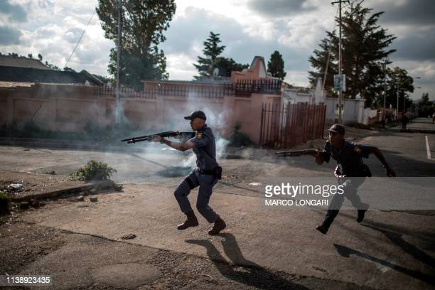 TOPSHOT South African police officers fire rubber bullet as they chase protestors in the streets of Johannesburg on April 23 2019 during a protest...