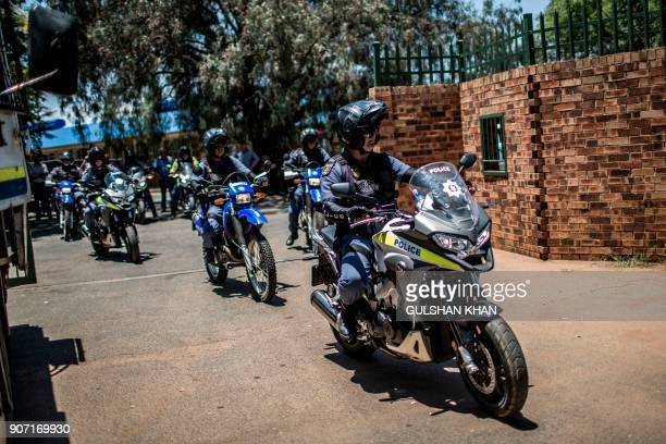 South African Police officers ride their motorbike outside the Horskool Overvaal school during a protest against the language and admission policies...