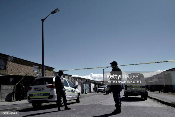 South African police officers stand behind a police cordon following a shooting of two alleged gang members in Manenberg Cape Town on October 18 2017...