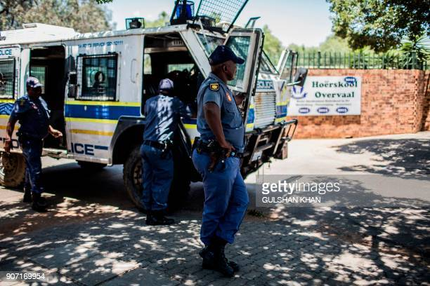 South African Police officers stand guard outside the Hoerskool Overvaal school during a protest against the language and admission policies on...