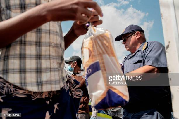 South African Police Service officers help the Cleveland Civic Committee volunteers during a food distribution in the Mangolongolo informal...